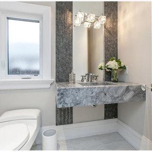 Foto di un bagno di servizio design di medie dimensioni con WC sospeso, piastrelle grigie, piastrelle in pietra, pareti grigie, pavimento con piastrelle in ceramica, lavabo integrato, pavimento bianco, top in marmo e top grigio