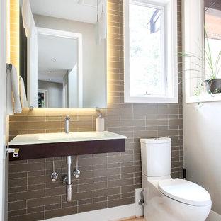 Immagine di un bagno di servizio contemporaneo con lavabo sospeso, WC a due pezzi, piastrelle grigie, piastrelle di vetro e top in vetro