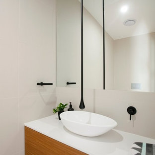Photo of a contemporary powder room in Sunshine Coast with flat-panel cabinets, medium wood cabinets and a vessel sink.