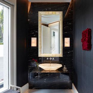 На фото: большой туалет в современном стиле с плоскими фасадами, черными фасадами, черной плиткой, черными стенами, настольной раковиной, серым полом, черной столешницей и встроенной тумбой