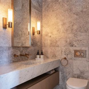 Idées déco pour un WC et toilettes contemporain avec un placard à porte affleurante, des portes de placard en bois brun, un WC suspendu, un carrelage gris, un lavabo intégré, un sol gris et un plan de toilette gris.