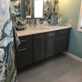 Inspiration for a small contemporary cloakroom in Other with flat-panel cabinets, grey cabinets, a one-piece toilet, grey tiles, blue walls, porcelain flooring, a submerged sink, recycled glass worktops and grey floors.