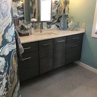 Idée de décoration pour un petit WC et toilettes design avec un placard à porte plane, des portes de placard grises, un WC à poser, un carrelage gris, un mur bleu, un sol en carrelage de porcelaine, un lavabo encastré, un plan de toilette en verre recyclé et un sol gris.
