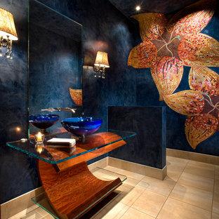 На фото: туалет в современном стиле с плиткой мозаикой, синими стенами, настольной раковиной, стеклянной столешницей, бежевым полом и бежевой плиткой