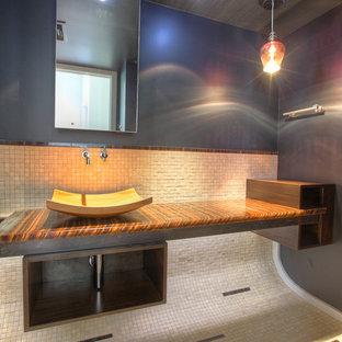 Новые идеи обустройства дома: туалет среднего размера в современном стиле с настольной раковиной, бежевой плиткой, коричневой плиткой, каменной плиткой, серыми стенами, полом из известняка, столешницей из оникса, бежевым полом и коричневой столешницей