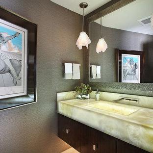 Idee per un bagno di servizio minimal con lavabo integrato, ante in legno bruno, top in onice e top beige