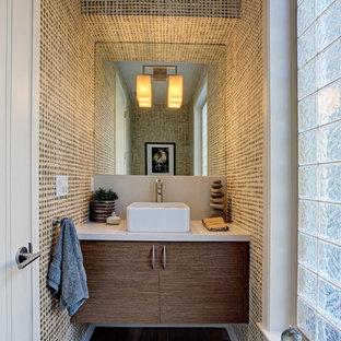 Ejemplo de aseo actual, pequeño, con armarios con paneles lisos, puertas de armario de madera en tonos medios, encimera de piedra caliza, paredes multicolor y suelo de madera oscura