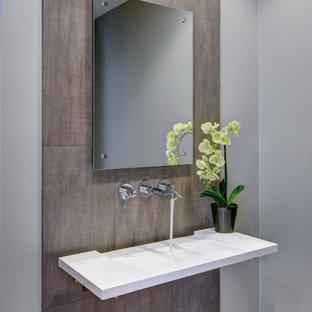 Immagine di un piccolo bagno di servizio design con lavabo sospeso, pareti grigie, top in superficie solida, piastrelle marroni e piastrelle in gres porcellanato