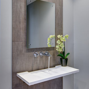 Idée de décoration pour un WC et toilettes design avec un lavabo suspendu, un plan de toilette en surface solide, un carrelage marron, des carreaux de porcelaine et un mur gris.