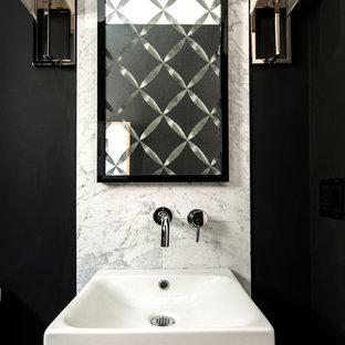 Idee per un bagno di servizio minimal con lavabo sospeso e piastrelle di marmo