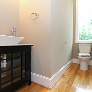 Small contemporary cloakroom in Raleigh with a vessel sink, glass-front cabinets, black cabinets, a one-piece toilet, grey walls and light hardwood flooring.