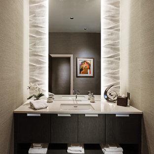 Cette photo montre un petit WC et toilettes tendance avec un lavabo encastré, un placard à porte plane, des portes de placard en bois sombre, un plan de toilette en quartz modifié, un mur beige, un carrelage beige, des carreaux de céramique, un sol en carrelage de porcelaine, un sol marron et un plan de toilette blanc.