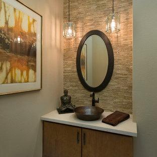 Стильный дизайн: маленький туалет в стиле фьюжн с плоскими фасадами, фасадами цвета дерева среднего тона, каменной плиткой, бежевыми стенами, полом из травертина, настольной раковиной, столешницей из искусственного камня и бежевой плиткой - последний тренд
