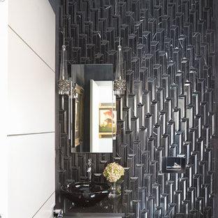 Réalisation d'un WC et toilettes design de taille moyenne avec un placard à porte plane, des portes de placard blanches, un WC suspendu, un carrelage noir, un mur noir, une vasque, un plan de toilette en surface solide et un plan de toilette gris.