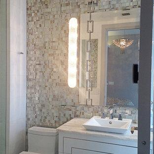 Пример оригинального дизайна: туалет среднего размера в современном стиле с плоскими фасадами, белыми фасадами, раздельным унитазом, разноцветной плиткой, стеклянной плиткой, белыми стенами, мраморной столешницей и настольной раковиной