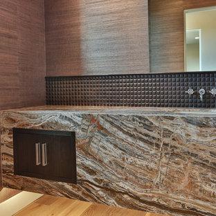 Пример оригинального дизайна: большой туалет в современном стиле с унитазом-моноблоком, коричневой плиткой, каменной плиткой, коричневыми стенами, паркетным полом среднего тона, врезной раковиной и столешницей из гранита