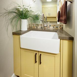 Cette photo montre un petit WC et toilettes chic avec un placard à porte shaker, des portes de placard jaunes, un carrelage beige, un carrelage marron, un carrelage gris, un mur beige, un sol en carreaux de ciment, un plan de toilette en granite et une plaque de galets.