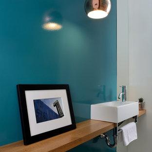 Источник вдохновения для домашнего уюта: маленький туалет в стиле модернизм с синими стенами, полом из керамической плитки, настольной раковиной, столешницей из дерева, серым полом и коричневой столешницей