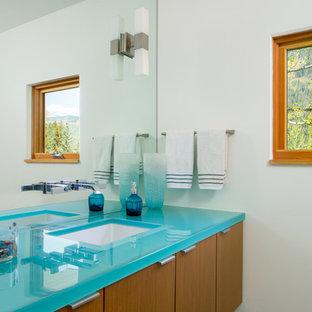 デンバーの中くらいのコンテンポラリースタイルのおしゃれなトイレ・洗面所 (アンダーカウンター洗面器、フラットパネル扉のキャビネット、中間色木目調キャビネット、ガラスの洗面台、白い壁、ターコイズの洗面カウンター) の写真