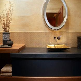 Cette photo montre un WC et toilettes tendance de taille moyenne avec des portes de placard noires, un carrelage beige, carrelage en mosaïque, un mur beige, une vasque, un plan de toilette en stéatite et un plan de toilette noir.