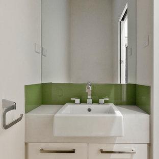 Diseño de aseo contemporáneo con armarios con paneles lisos, puertas de armario blancas, baldosas y/o azulejos verdes, baldosas y/o azulejos de vidrio laminado, paredes blancas, lavabo sobreencimera y encimera de cuarzo compacto