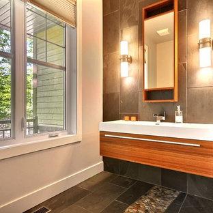モントリオールのコンテンポラリースタイルのおしゃれなトイレ・洗面所 (中間色木目調キャビネット、茶色いタイル、壁付け型シンク、スレートタイル) の写真