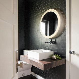 Inredning av ett modernt brun brunt badrum, med mörkt trägolv, träbänkskiva, svarta väggar och brunt golv