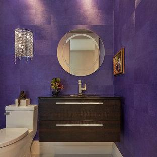 Стильный дизайн: туалет среднего размера в современном стиле с плоскими фасадами, темными деревянными фасадами, унитазом-моноблоком, фиолетовыми стенами, монолитной раковиной и белым полом - последний тренд