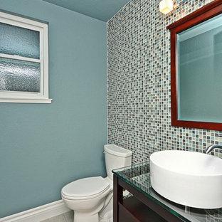 Идея дизайна: маленький туалет в современном стиле с фасадами островного типа, темными деревянными фасадами, унитазом-моноблоком, синей плиткой, зеленой плиткой, разноцветной плиткой, плиткой мозаикой, синими стенами, полом из керамической плитки, настольной раковиной, стеклянной столешницей и серым полом