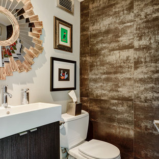 Inspiration for a mid-sized contemporary brown tile and stone tile powder room remodel in Columbus with a trough sink, flat-panel cabinets, dark wood cabinets, a two-piece toilet and white walls