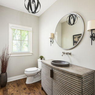 Example of a large classic dark wood floor and brown floor powder room design in Chicago with a vessel sink, furniture-like cabinets, brown cabinets, brown countertops and beige walls