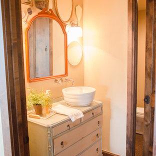 Idee per un piccolo bagno di servizio eclettico con ante lisce, piastrelle marroni, ante con finitura invecchiata, WC a due pezzi, pareti beige, pavimento con piastrelle a mosaico e lavabo a bacinella