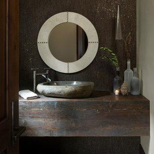 Ejemplo de aseo rústico con paredes marrones, lavabo sobreencimera, encimera de madera y encimeras marrones
