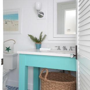 Immagine di un bagno di servizio stile marino di medie dimensioni con lavabo sottopiano, ante blu, top in quarzo composito, piastrelle blu, pareti bianche, WC a due pezzi, pavimento in cementine, pavimento multicolore e top bianco