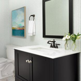 Foto di un bagno di servizio stile marinaro di medie dimensioni con ante con riquadro incassato, ante marroni, WC a due pezzi, pareti multicolore, pavimento in laminato, lavabo da incasso, top in quarzo composito, pavimento grigio e top bianco