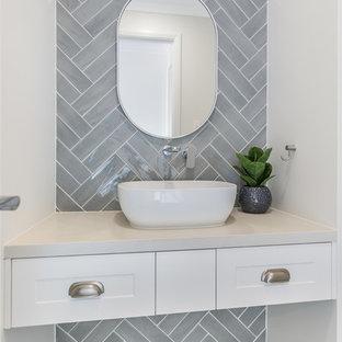 Пример оригинального дизайна: маленький туалет в классическом стиле с фасадами в стиле шейкер, белыми фасадами, унитазом-моноблоком, серой плиткой, керамической плиткой, белыми стенами, полом из керамической плитки, настольной раковиной, столешницей из искусственного кварца, серым полом и белой столешницей