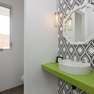 На фото: туалеты в современном стиле с настольной раковиной, белыми стенами, бетонным полом, коричневым полом и зеленой столешницей