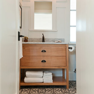 This is an example of a small rustic cloakroom in Vancouver with medium wood cabinets, a one-piece toilet, multi-coloured tiles, white walls, concrete flooring, a submerged sink, marble worktops and flat-panel cabinets.