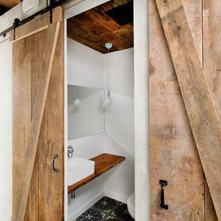 Idee per un bagno di servizio industriale con lavabo a bacinella, top in legno, pareti bianche e top marrone