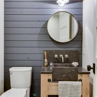 ミネアポリスの小さいカントリー風おしゃれなトイレ・洗面所 (家具調キャビネット、茶色いキャビネット、分離型トイレ、青いタイル、青い壁、ライムストーンの床、オーバーカウンターシンク、御影石の洗面台、青い床、黒い洗面カウンター) の写真