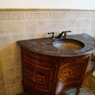 Inspiration for a medium sized mediterranean cloakroom in Philadelphia with a two-piece toilet, beige tiles, ceramic tiles, beige walls, slate flooring, a submerged sink, brown floors, freestanding cabinets and dark wood cabinets.