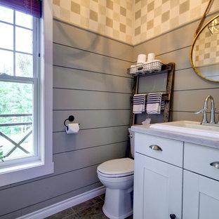 Exemple d'un petit WC et toilettes nature avec un placard à porte shaker, des portes de placard blanches, un WC séparé, un mur vert, un sol en carrelage de céramique, un lavabo posé, un plan de toilette en bois, un sol marron et un plan de toilette beige.