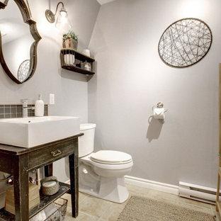 Свежая идея для дизайна: туалет в стиле кантри с открытыми фасадами, черными фасадами, раздельным унитазом, черной плиткой, керамической плиткой, серыми стенами, полом из керамической плитки, настольной раковиной, столешницей из дерева, бежевым полом и черной столешницей - отличное фото интерьера