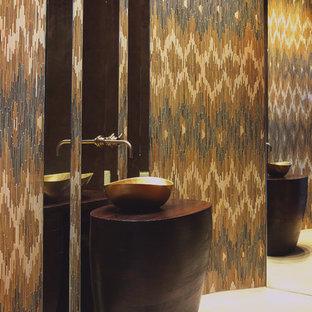 Неиссякаемый источник вдохновения для домашнего уюта: маленький туалет в современном стиле с настольной раковиной, столешницей из дерева, разноцветной плиткой, коричневыми стенами, полом из известняка и коричневой столешницей