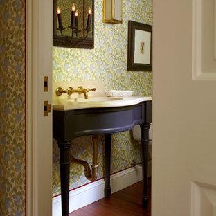 Foto di un piccolo bagno di servizio tradizionale con consolle stile comò, ante grigie, pavimento in legno massello medio, lavabo sottopiano, top in pietra calcarea, WC a due pezzi, pareti multicolore e pavimento marrone