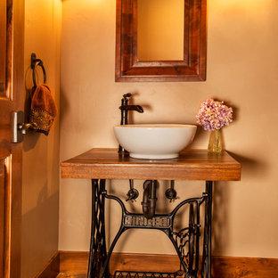 Diseño de aseo rural, pequeño, con armarios abiertos, puertas de armario negras, paredes beige, suelo de pizarra, lavabo sobreencimera, encimera de madera, suelo marrón y encimeras marrones