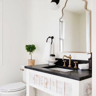 Inspiration for a country multicolored floor powder room remodel in Minneapolis with open cabinets, distressed cabinets, white walls, an undermount sink and black countertops
