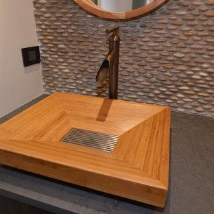 Foto på ett funkis toalett, med skåp i mörkt trä, kakel i småsten och ett piedestal handfat
