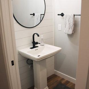 Réalisation d'un petit WC et toilettes champêtre avec un WC séparé, un mur multicolore, un sol en bois brun, un lavabo de ferme et un sol marron.