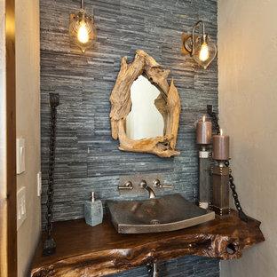 Cette photo montre un WC et toilettes montagne avec un carrelage de pierre, une vasque, un carrelage gris, un mur beige, un sol en bois foncé, un plan de toilette en bois, un sol marron et un plan de toilette marron.